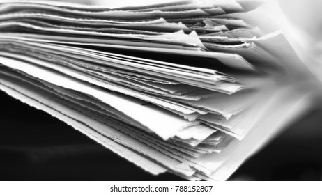 Newspapers. Pile of old English news pages on the table. Paper texture, blurred background