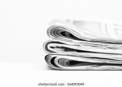 Newspapers. Stack of newspapers. The pile of news are on a white surface. Image in black and white.