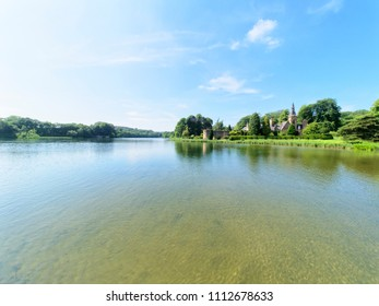 Newstead, England - June 10 2018: Newstead Abbey lake and a building known as The Fort. The rippled water of the lake reflects the clouds and tree lined lake shore.
