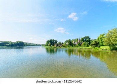 Newstead, England - June 10 2018: Newstead Abbey lake and The Fort. The rippled water of the lake reflects the clouds and tree lined lake shore.