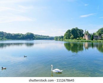 Newstead, England - June 10 2018: In the grounds of Newstead Abbey the Fort  sits on the shore of a lake. The rippled water of the lake reflects the clouds.  A swan and two ducks swim on the lake