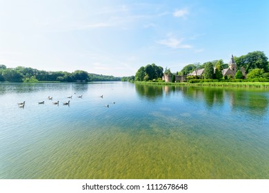 Newstead, England - June 10 2018: In the grounds of Newstead Abbey a group of Canada Geese swim across the lake towards a building called The Fort.