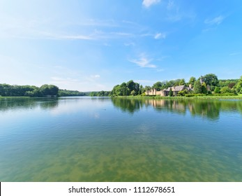 Newstead, England - June 10 2018: In Newstead Abbey grounds the Fort sits on the shore of a lake.The rippled water of the lake reflects the clouds and tree lined lake shore.