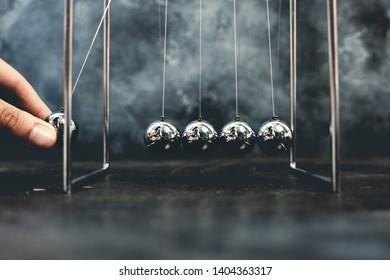 Newton cradle pendulums steel kinetic balls hand pulling one