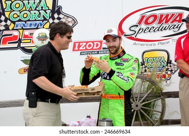 Newton Iowa, USA - June 23, 2013: Indycar Iowa Corn 250 race Iowa Speedway. Pizza Ranch Victory Circle. Race winner James Hinchcliffe, Canada, GoDaddy, Chevrolet, Andretti Autosport eating pizza.