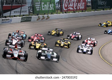 Newton Iowa, USA - June 23, 2013: Indycar Iowa Corn 250 race Iowa Speedway Simona de Silvestro front and center of many. Large group of INDYCAR racers in corner. Pack of dozens cars at start of race