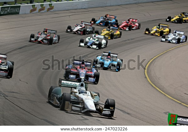 Newton Iowa, USA - June 23, 2013: Indycar Iowa Corn 250 race Iowa Speedway Ed Carpenter and field of eleven Dallara Indycar race cars. Group of Indy Cars race track corner.