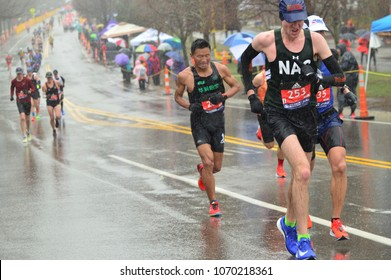 Newton, MA; USA, April 16, 2018 Marathon runners brave the rain, cold, and wind while climbing Heartbreak Hill in Newton, Massachusetts during the Boston Marathon