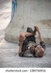 Newtown, India- April 15,2019 A old man is homeless or beggar sleeping sleeping on the ground beside street or walkway.