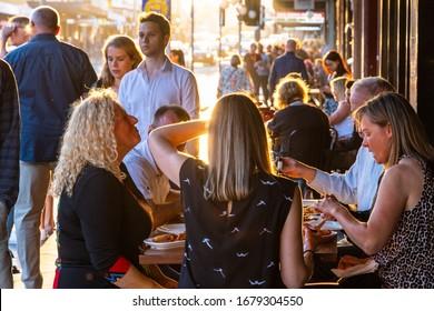 Newtown, Sydney, NSW - 27 10 2018: Friends eating al fresco at sunset