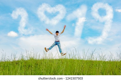 Newyear 2019 Clouds.Happiness young people jumping blue sky to 2019 new year. Graduation in 2019 years with Congratulation concept in green Meadow.