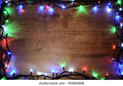 New-year electric garland on a wooden background. Bright bulbs on a wooden table Christmas tree.