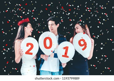 Newyear party ,celebration party group of asian young people holding balloon numbers 2019 happy and funny concept