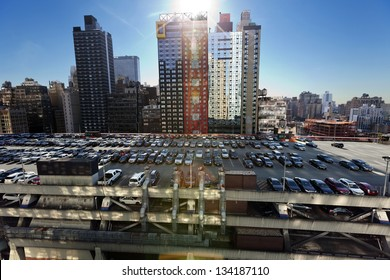 NEW-YORK - NOVEMBER 6th, 2012: Wide angle view of the NYC Port Authority's (central bus station) rooftop parking lot, almost full with cars, and surrounded by midtown skyscrapers.