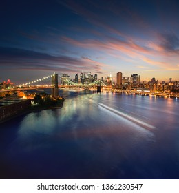 NewYork skyline at sunset with beautiful cloudscape. Wide angle image of New York Manhattan with East river in front. Brooklyn bridge connecting Manhattan and Brooklyn at night.