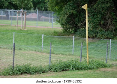 next to the fence is a yellow flag made of metal