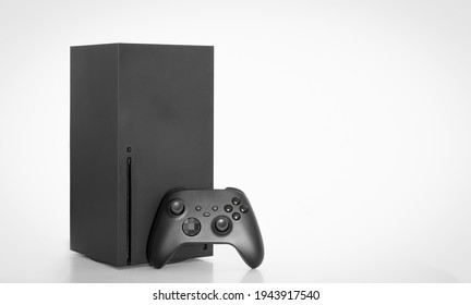 Next Generation game console and controller on white background.