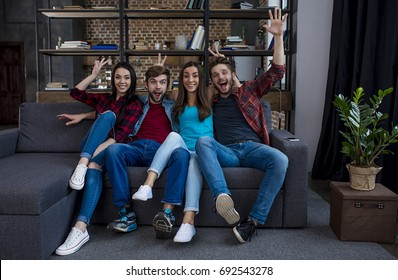 The next goal is scored in the goal. Four beautiful and cheerful friends sitting on the sofa at home watching football and cheering for their team