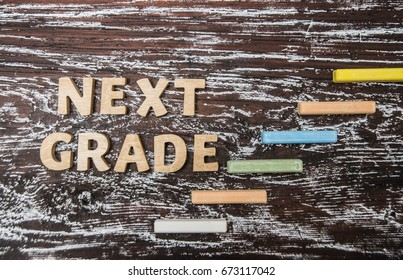 next grade, level, back to school - wooden words on wood chalkboard,  stairway made from colorful chalk next step,  grade, level - idea, sign, symbol, concept. 1th september.