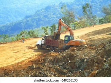 Next to Lake Izabal, Guatemala - 30 March, 2017: Excavator CASE and truck working on the ore stockpile yard in the cloud of dust . Heavy machinery equipment.