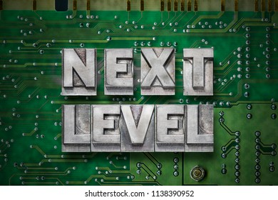 next level phrase made from metallic letterpress blocks on the pc board background