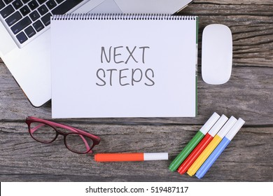 NEXT STEPS text on wooden desk with tablet pc and keyboard