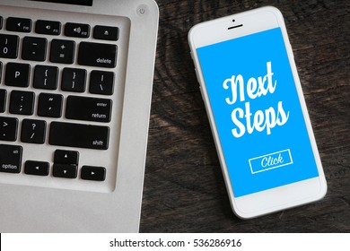 """""""Next Steps"""" words on smartphone with a laptop near it - website, multimedia and business concept"""
