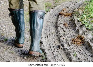 À côté de la piste. Un homme marche avec ses bottes en caoutchouc vert à côté d'une piste de pneu à travers la boue.