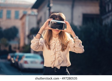 Next wave of new digital media. Augmented, Virtual and Mixed Reality, 360 video and 3D video. Happy young girl testing virtual reality glasses VR headset outside, beautiful autumn morning sunlight