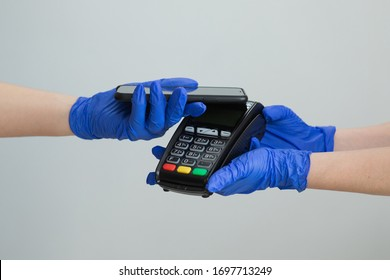 Nfc cellhone of female buyer with cashless wallet of e-money for pos card reader and checkout. Woman in gloves applies smartphone to terminal performing successful contactless payment