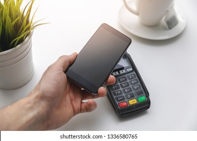 nfc contactless payments - hand holding phone above payment terminal
