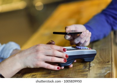 NFC Near Field Communication Mobile Payment. Hand holding smartphone paying on EDC machine.