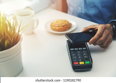 nfc payment with mobile phone at cafe