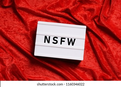 nfsw is internet slang for not safe for work or adult content containing nudity pornography profanity or violence, abstract censorship concept with text on lightbox or light box sign on red velvet