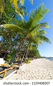 Ngapali beach with white sand, blue sky and palm trees, in Myanmar