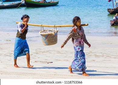 NGAPALI, MYANMAR - DECEMBER 03, 2014: women carrying sea fish on the beach in Thandwe village, Ngapali beach, Myanmar
