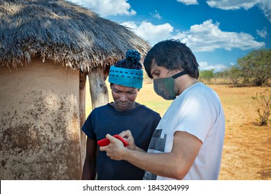 ngo Caucasian young man showing in his phone new developments to an african villager