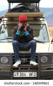 NGORONGORO CALDERA, TANZANIA - SEPTEMBER 15: An African man talks on the cell phone while sitting on a safari truck in the Ngorongoro Caldera, Tanzania on September 15, 2012.