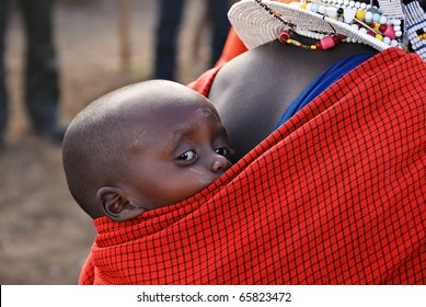 NGORONGORO CONSERVATION AREA, TANZANIA - JANUARY 24: Unidentified African child from Masai tribe on January 24, 2008.  Very young child is on the back of his mother
