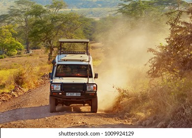 Ngorongoro conservation, Tanzania, Jun 29, 2016: Safari car SUV 4x4 dirty off road in savannah. Open roof 4wd jeep on african reserve landscape background. Common Africa countryside auto, horizontal