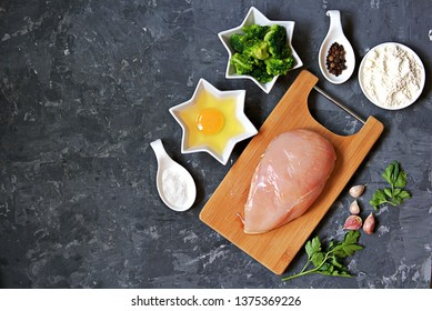 ngredients for cooking chopped chicken cutlets or rissole with broccoli: raw chicken, broccoli, wheat flour, egg, salt, pepper, garlic, parsley. Top view, copy space.