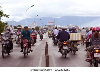 NHA TRANG CITY, VIET NAM- FEB 11: Dense, crowed scene of city traffic in rush hour, crowd of people wear helmet, transport by motorcycle, Vietnam, Feb 11, 2014