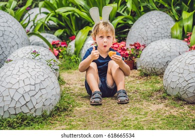 Nha Trang, Vietnam -15 March 2017: Cute little kid boy with bunny ears having fun with traditional Easter eggs hunt, outdoors. Celebrating Easter holiday. Toddler finding, colorful eggs.