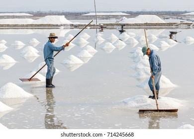 NHA TRANG, VIETNAM - 4/12/2016: Two men organize salt into piles at the Hon Khoi salt fields in Nha Trang, Vietnam.