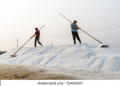 NHA TRANG, VIETNAM - 4/12/2016: Workers shape a salt pile at the Hon Khoi salt fields in Nha Trang, Vietnam.