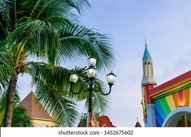 NHA TRANG, VIETNAM - APRIL 16, 2019: Vintage lamp with a rainbow wall and a tropical palm in an amusement park at evening