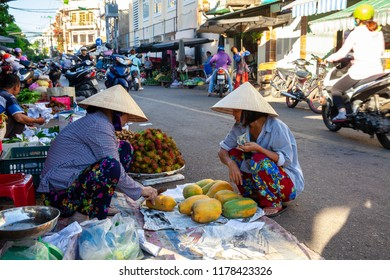 NHA TRANG, VIETNAM - AUGUST 06: A senior woman sells papaya at the street market on August 06, 2018 in Nha Trang, Vietnam.