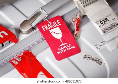 Nha Trang, Vietnam - August 16, 2016: Closeup view of bright red luggage tag (Fragile, Handle with care) attached to white plastic suitcase at airport of Cam Ranh.