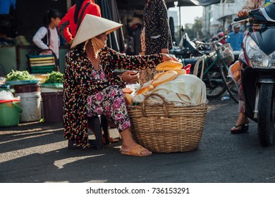 Nha Trang, Vietnam - July 14, 2016: Vietnamese woman sells baguette at the morning market in Nha Trang, Vietnam on July 14, 2016.