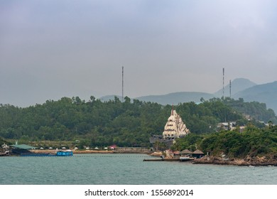 Nha Trang, Vietnam - March 11, 2019: Evening, Tall ship of scary pirates in fun and amusement park  of Vinpearl resort on Vinh Nguyen Island. Forested hills, antennas and resort huts, docks and beache